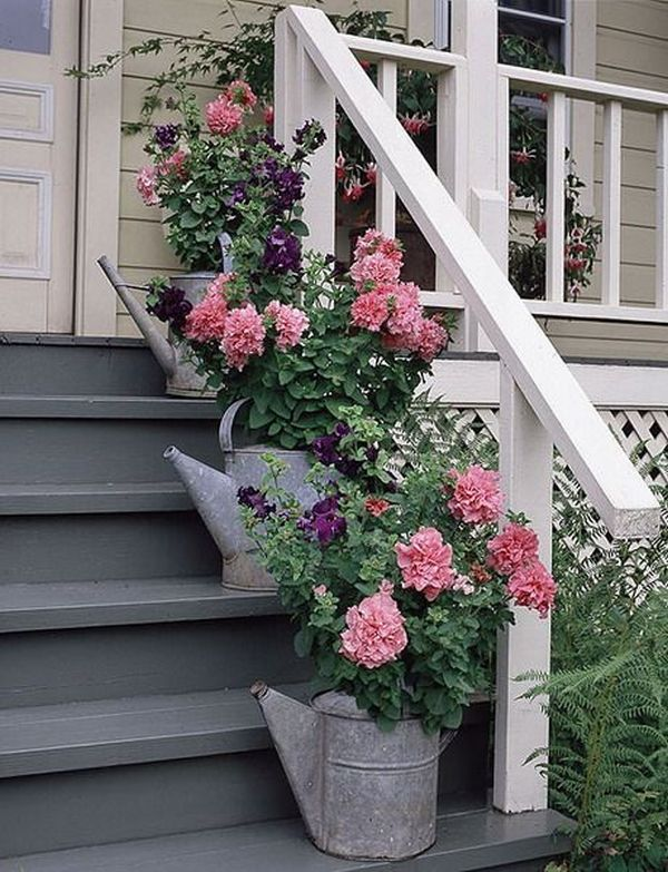 old tin watering cans with pink flowers on the front porch steps