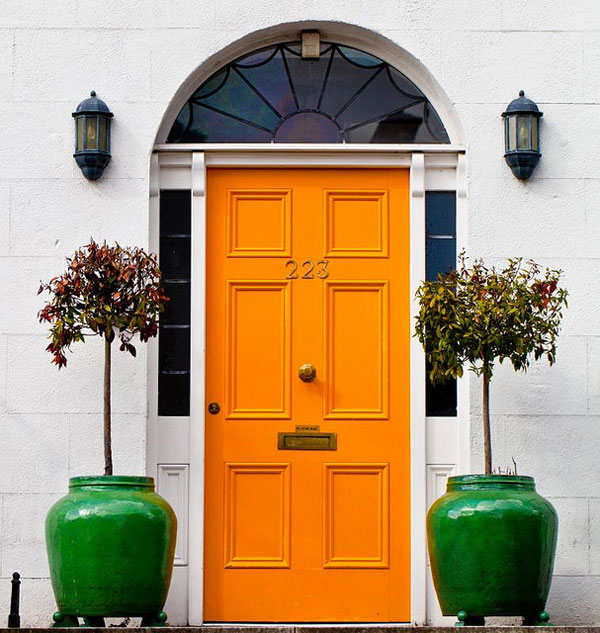 Front porch flower pot ideas-bright orange front door with glazed green pots and topiary trees
